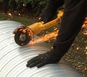 Engineer cutting ducting with an angle grinder