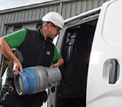 Refrigeration engineer loading gas bottle into van